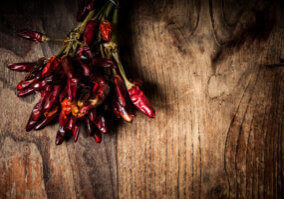dried hot red chilies on brown textured wood
