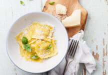 Ravioli pasta with cream sauce, basil and parmesan cheese on olive wood cutting board