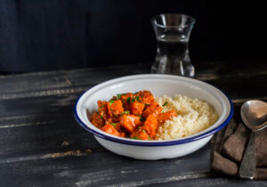 Healthy vegetarian lunch - pumpkin stew and couscous in a white enamel bowl on a dark wooden board.  Rustic style