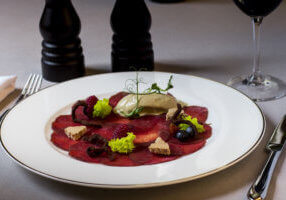 carpaccio with deer served on white plate, decorated