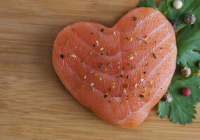 Heart shaped salmon with wooden backgroud